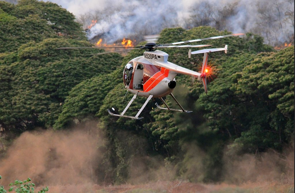 A helicopter circles a wildfire in Kauaʻi, where these fires are becoming increasingly common during drier summer months. Photo by Brian Howell, Flickr Commons.